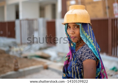 Gurgaon, India - May 14 2019: Portrait of a woman labourer with the helmet working in an urban construction site. #1410539822
