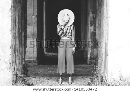 Stylish woman hides her face behind a straw hat. Trend creative brash concept. Monochrome image. Glossy vogue background Royalty-Free Stock Photo #1410553472