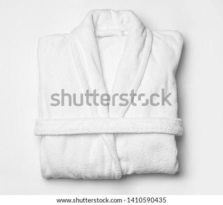 Clean folded bathrobe on white background, top view Royalty-Free Stock Photo #1410590435