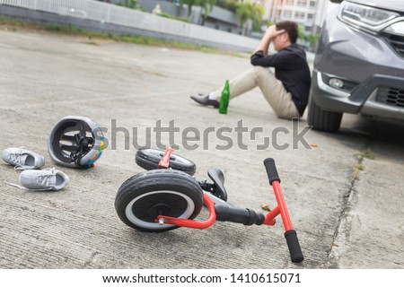scared and stressed desperate drunken driver and bottle of beer in front of automobile crash car with child bike after traffic accident in city road