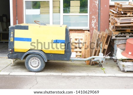 Yellow portable powerhouse or portable compressor with generator next to a pile of wooden pallets. #1410629069