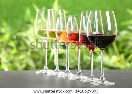 Row of glasses with different wines on grey table against blurred background. Space for text #1410629393