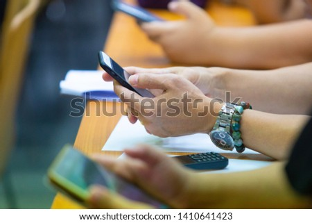 The woman's hand is using the smartphone during the class,business, financial,stock market,applications concept. #1410641423