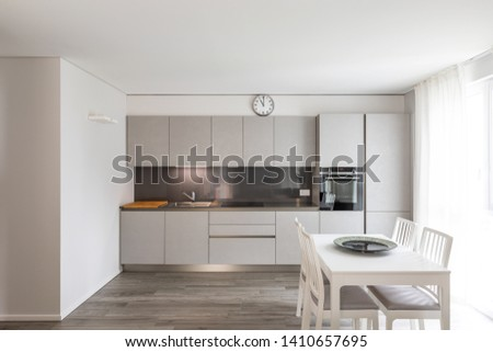 Modern gray kitchen with white chair and table. Nobody inside #1410657695