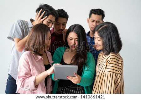Asian women hold tablets with friends and watch soccer matches #1410661421