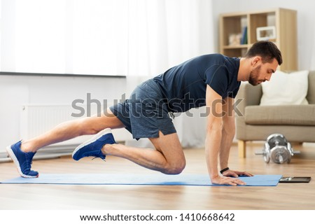 sport, fitness and healthy lifestyle concept - man with tablet computer doing running plank exercise at home #1410668642