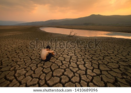 Sad Children or young man sitting on cracked earth near drying river metaphor water crisis, climate change, Drought and Environment disaster #1410689096