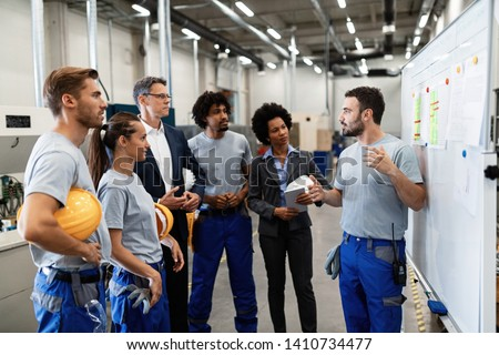 Manual worker communicating with company leaders and his coworkers during business presentation in a factory.  #1410734477