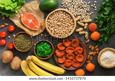 Healthy foods high in potassium. A variety of legumes, salmon, fruits, vegetables, dried apricots, seaweed chuka and nuts on a dark background. Top view, flat lay #1410737870
