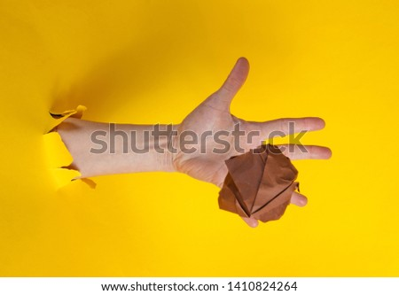 Female hand throws brown crumpled ball of paper through the torn yellow paper background. Minimalistic concept #1410824264