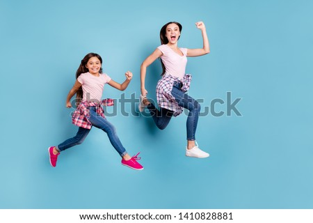 Full length body size view portrait of two nice attractive cheerful cheery ecstatic straight-haired girls hipster outfit running fast isolated on bright vivid shine blue turquoise background #1410828881