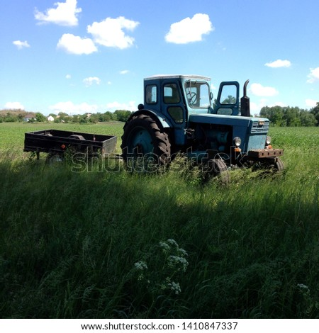 Macro photo transport retro vintage tractor. Texture background blue tractor with trailer. Rural old tractor stands in a field against a blue sky. #1410847337
