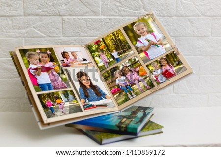 High angle view open book with album at home Royalty-Free Stock Photo #1410859172