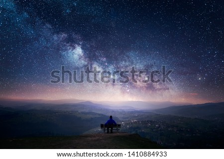 A man sitting on a bench staring at a starry sky with a Milky Way and a mountain landscape #1410884933