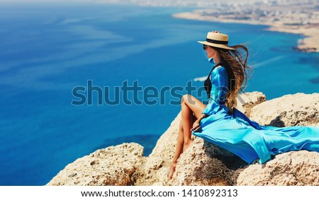 Summer lifestyle fashion image of happy stunning woman sitting on the cliff above the sea. Enjoying life and looking at the sea. Turquoise sea background. Wearing stylish dress, straw hat, sunglasses #1410892313