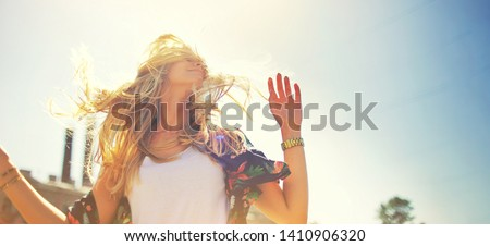 Attractive happy young woman in white t shirt flying hair enjoying her free time at sunset outdoor. Beauty blonde girl portrait at summer. Freedom lifestyle springtime concept. Sun glow on background