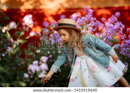 Little girl outdoor portrait in a pink flowers at sunset #1410919640