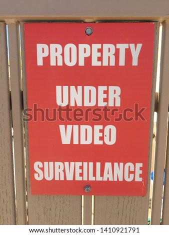 Property under video surveillance sign warning poster camera watch security safety private red white wood fence close up macro