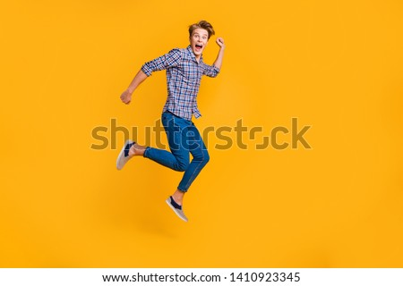 Full length body size view portrait of nice attractive cheerful cheery optimistic guy in checked shirt having fun running fast hurry rush isolated over bright vivid shine yellow background #1410923345