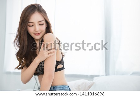 Portrait of asian woman in black lace bra lingerie underwear boudoir. Beauty smiling asian girl applying lotion on shoulder arm skin in her morning routine. Sexy girl modern asia lifestyle concept  #1411016696
