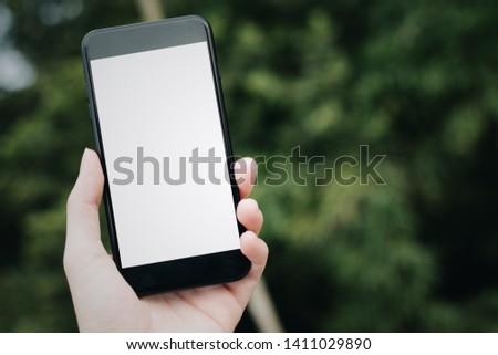 Cropped hand, Close-up of male hand holding Mobile Phone with blank screen for your text message or content, man's hand using cellphone with empty display in green city, bokeh light, Mockup image. #1411029890