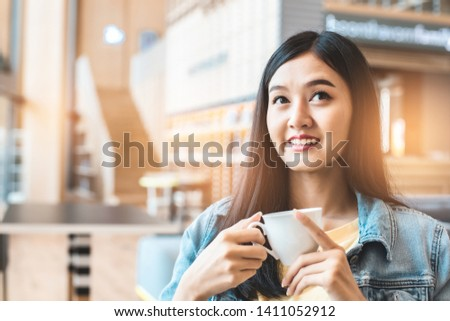 Asian woman in a cafe drinking coffee .Portrait of Asian woman smiling in coffee shop cafe vintage color tone. #1411052912