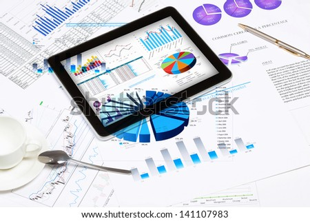Image of cup of coffee and ipad laying on business documents