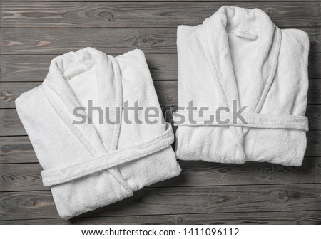 Flat lay composition with folded bathrobes on wooden background Royalty-Free Stock Photo #1411096112