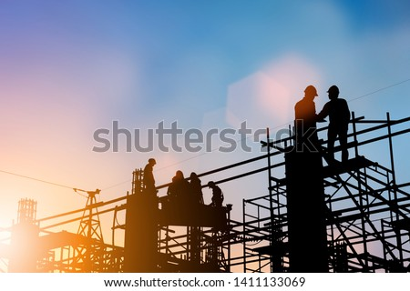 Silhouette of engineer and construction team working at site over blurred background for industry background with Light fair. #1411133069