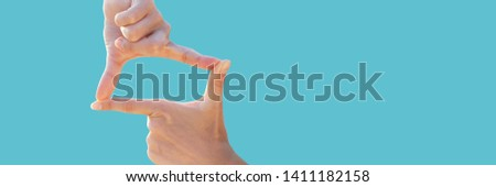 Women's hands making photo frame composition. Professional gesture of photographer. Isolated on blue background. Long banner format