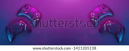 Gamepads on violet table background. Gamer concept.