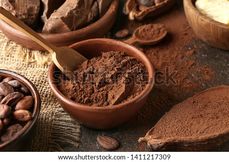 Bowl with cocoa powder on table Royalty-Free Stock Photo #1411217309
