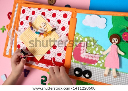 CHILDREN'S LEARNING DEVELOPING BOOK, SEWING FROM A FABRIC. CHILD PLAYS WITH HANDS WITH A BOOK.