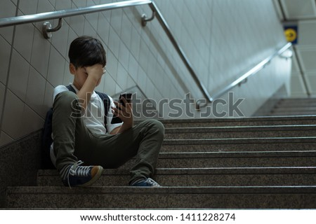 Cyber bullying concept. Young Asian preteen/teenage boy sitting at stair, covering his face with hand, other hand holding smartphone. Alone, stressed, frustrated, overwhelmed, crying, depressed, tech. #1411228274