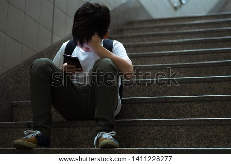 Cyberbullying concept. Young Asian preteen boy sitting at stair, covering his face with hands and other hand holding smartphone. Alone, stressed, frustrated, overwhelmed with online bullying. #1411228277