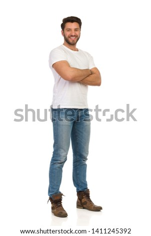 Smiling handsome man in jeans and white t-shirt is standing with arms crossed and looking at camera. Full length studio shot isolated on white. #1411245392