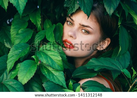 Female face in green leaves of bushes                    #1411312148