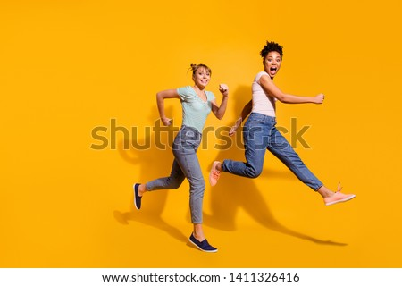 Full length body size view photo cheerful playful youth free time weekend holiday summer active race hurry childish curly haircut stylish trendy t-shirt jeans clothing isolated yellow background #1411326416