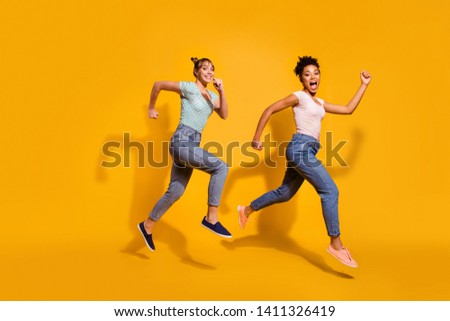 Full length body size view photo positive cheerful carefree student free time weekend summer energy race content excited childish curly haircut stylish trendy jeans clothing isolated yellow background #1411326419