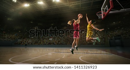 Female basketball players fight for the ball. Basketball player makes slam dunk on big professional arena during the game #1411326923