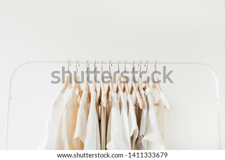Minimal fashion clothes concept. Female blouses and t-shirts on hanger on white background. Fashion blog, website, social media hero header. Royalty-Free Stock Photo #1411333679