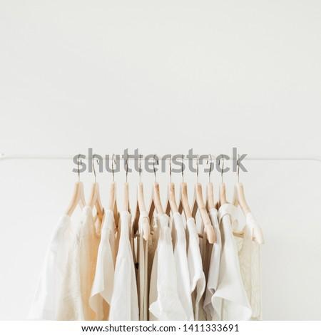 Feminine clothes on hanger. Minimal fashion composition on white background. #1411333691
