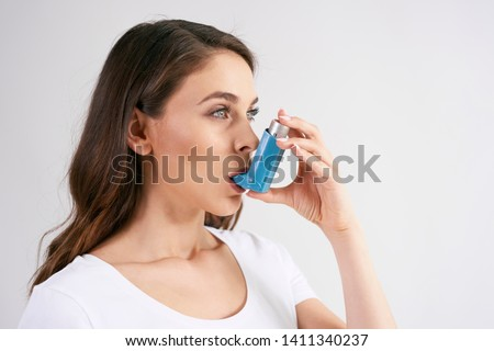 Asthmatic woman using an asthma inhaler during asthma attacks  Royalty-Free Stock Photo #1411340237
