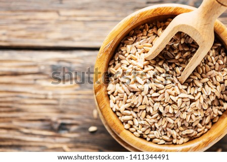 Uncooked pearl barley on the wooden table, rustic style and selective focus image #1411344491