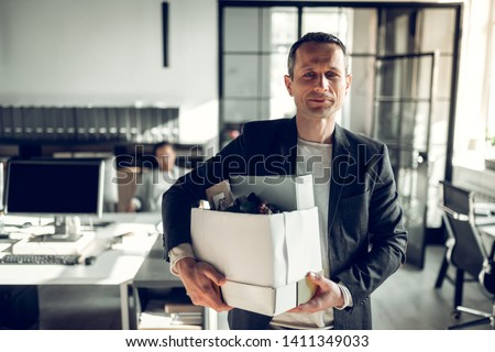 Economist leaving office. Handsome economist leaving the office taking his box with different things #1411349033