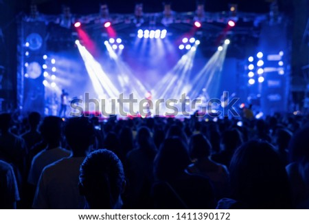 Silhouettes of crowd, group of people, cheering in live music concert in front of colorful stage lights. #1411390172