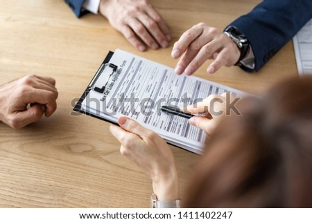 overhead view of woman holding clipboard and pen near car dealer and man  #1411402247