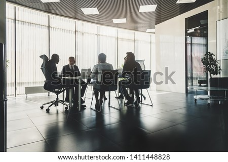 Silhouettes of people sitting at the table. A team of young businessmen working and communicating together in an office. Corporate businessteam and manager in a meeting. #1411448828
