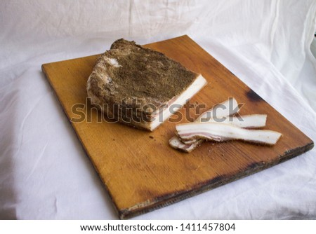 Salted lard on a wooden board. Chopped bacon. #1411457804