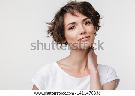 Portrait of pretty woman with short brown hair in basic t-shirt looking at camera while standing isolated over white background #1411470836